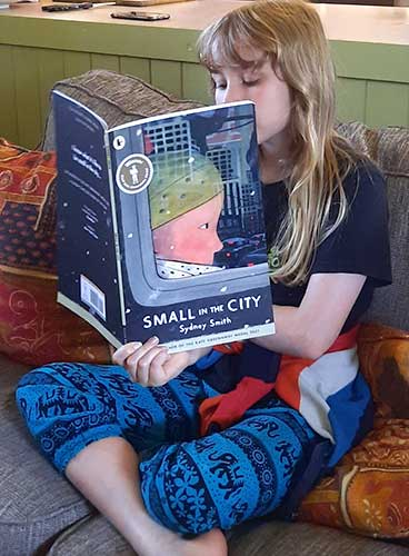Iona, 9, reads Small in the City by Sydney Smith