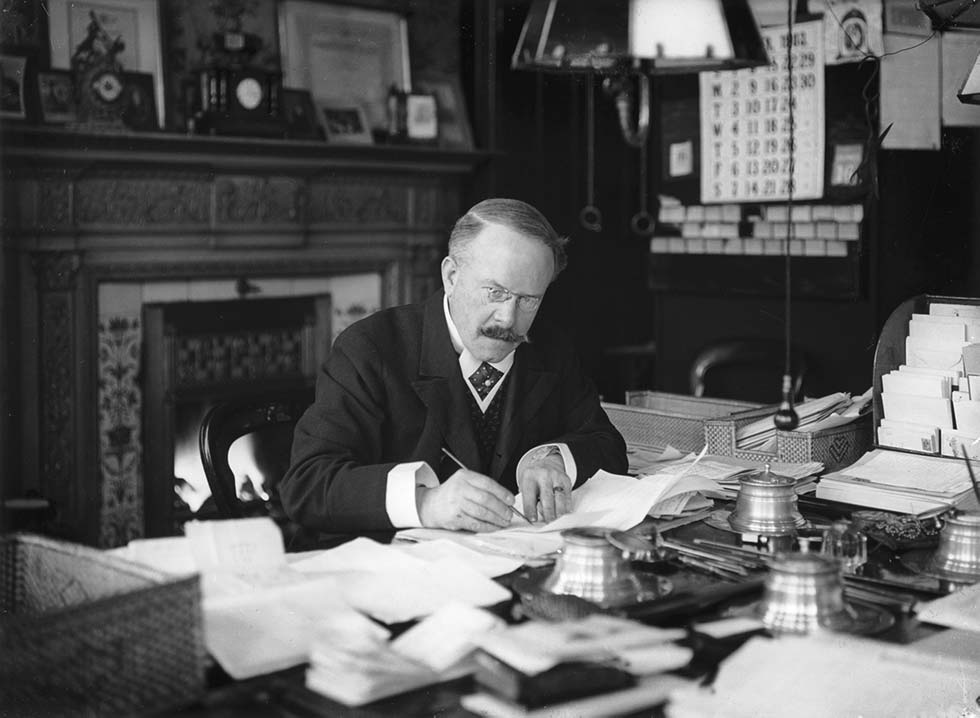 Dr Thomas Barnardo writing at his desk